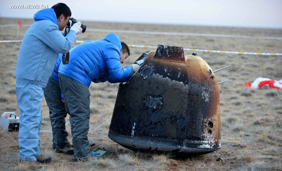 Ground teams in China inspect the a space capsule after its return from a flight around the moon. Credit: Xinhua/Ren Junchuan