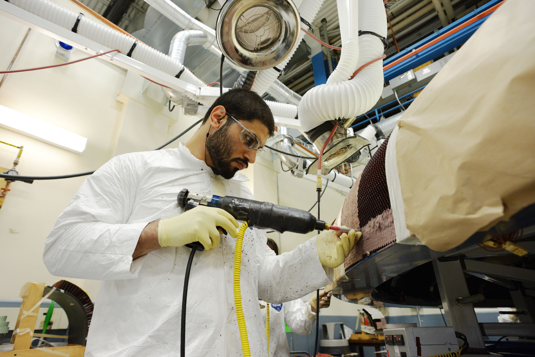 """Textron technicians apply the Avcoat material by """"gunning"""" the material into each of the 330,000 individual cells of the honeycomb structure. Credit: NASA"""