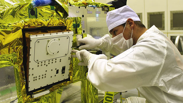 A technician installs the MASCOT lander into the Hayabusa 2 spacecraft before launching to an asteroid. Credit: DLR