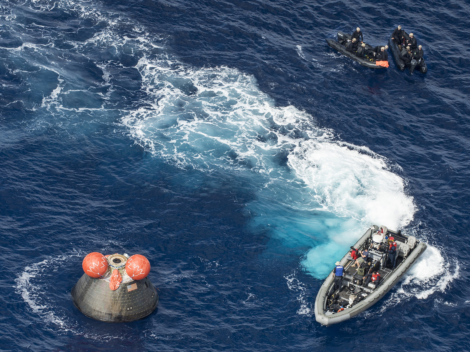 U.S. Navy divers approach the Orion spacecraft in the Pacific Ocean. Two of the capsule's five self-righting airbags are inflated. Credit: U.S. Navy photo by Mass Communication Specialist 1st Class Charles White