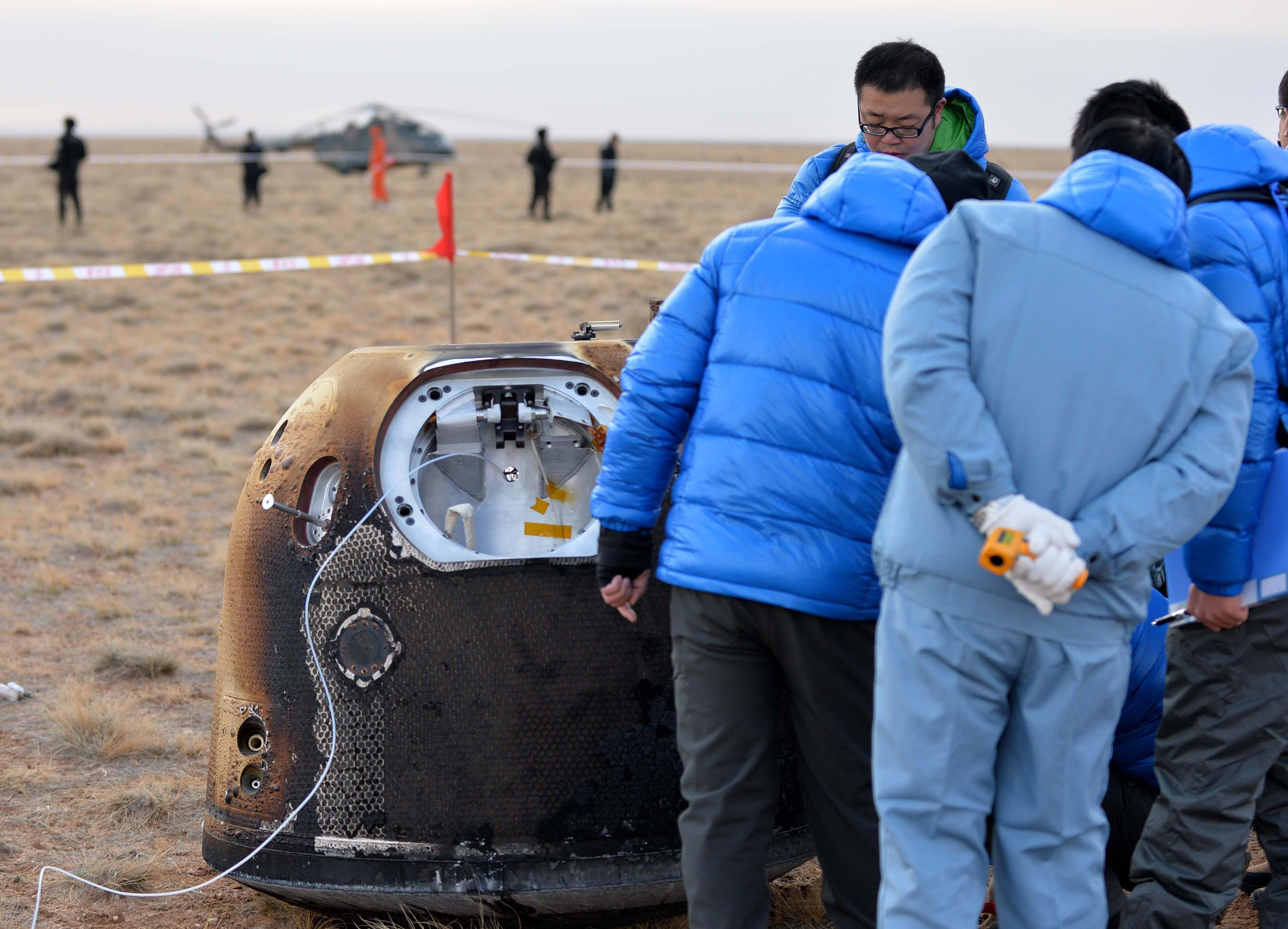 Chinese officials inspect a landing capsule deployed from the Chang'e 5 pathfinder probe after landing Oct. 31. Credit: Xinhua