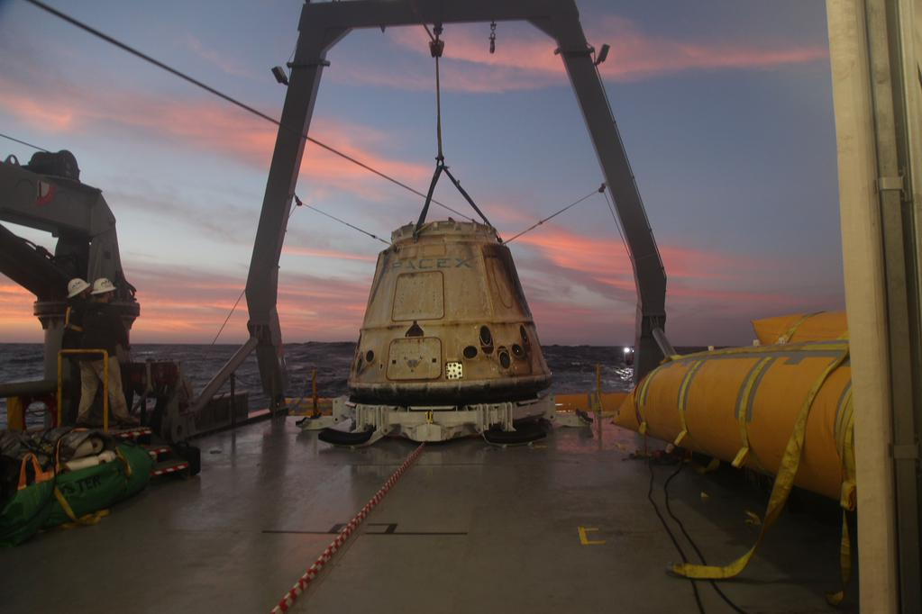 The Dragon spacecraft is lifted on the deck of a recovery ship in the Pacific Ocean. Credit: SpaceX via Elon Musk