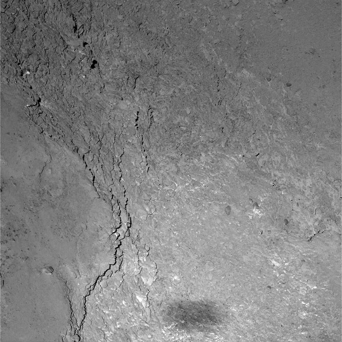 Close view of a 228 x 228 m region on Comet 67P/Churyumov-Gerasimenko, as seen by the OSIRIS narrow-angle camera during Rosetta's flyby at 12:39 UT on 14 February 2015. The image was taken six kilometers above the comet's surface, and the image resolution is just 11 cm/pixel. Rosetta's fuzzy shadow, measuring approximately 20 x 50 meters, is seen at the bottom of the image. Credit: ESA/Rosetta/MPS for OSIRIS Team MPS/UPD/LAM/IAA/SSO/INTA/UPM/DASP/IDA