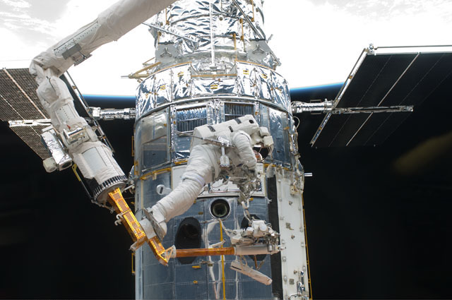 Astronaut Drew Feutel is perched on the end of the space shuttle's robotic arm during the 2009 Hubble repair mission. Credit: NASA
