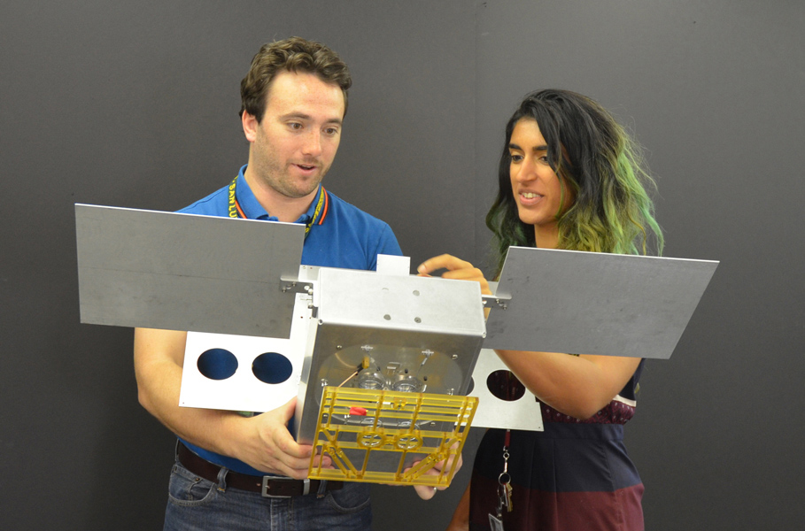 Mechanical engineer Joel Steinkraus and systems engineer Farah Alibay hold a full-scale mechanical mock-up of a MarCO CubeSat. Credit: NASA/JPL-Caltech