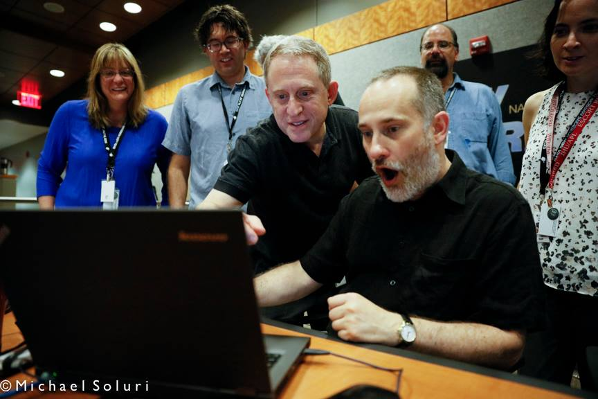Alan Stern (center) and members of the New Horizons science team react to seeing new images of Pluto for the first time. Credit: Michael Soluri
