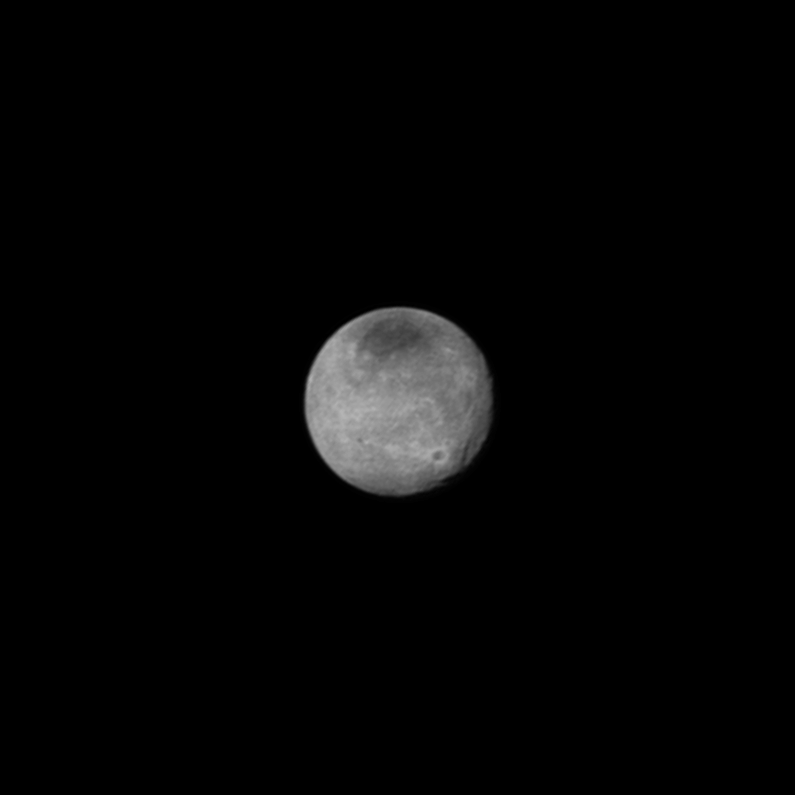 Pluto's moon Charon, seen here in true colour, has a dark, red-tinted feature on its north pole. Credit: NASA/JHUAPL/SWRI