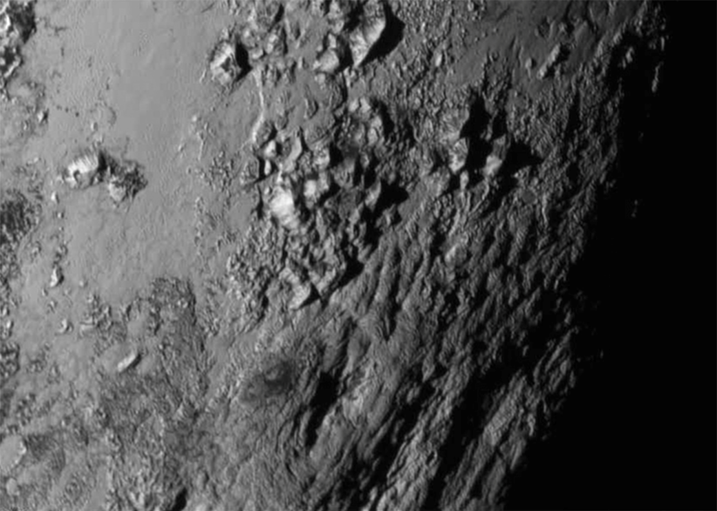 A snapshot of Pluto shows fresh deposits of water ice bedrock and 11,000-foot mountains, revealing evidence Pluto's surface is one of the youngest in the solar system. Photo credit: NASA/JHUAPL/SWRI