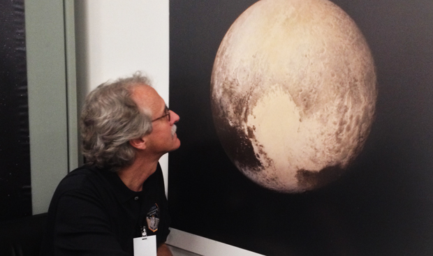 New Horizons scientist John Spencer inspects a poster print of the mission's latest Pluto image Tuesday. Credit: Stephen Clark/Spaceflight Now