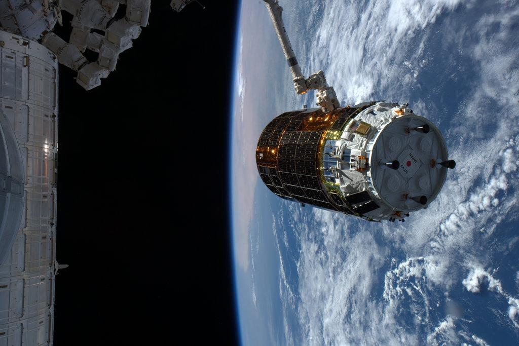 Japan's fifth HTV cargo freighter is seen in the grasp of the space station's robotic arm Monday. Credit: NASA/JAXA/Kimiya Yui