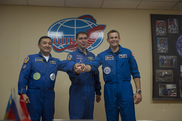 Aidyn Aimbetov, Sergey Volkov and Andreas Mogensen (left to right) join hands before Wednesday's launch. Credit: ESA/S. Corvaja
