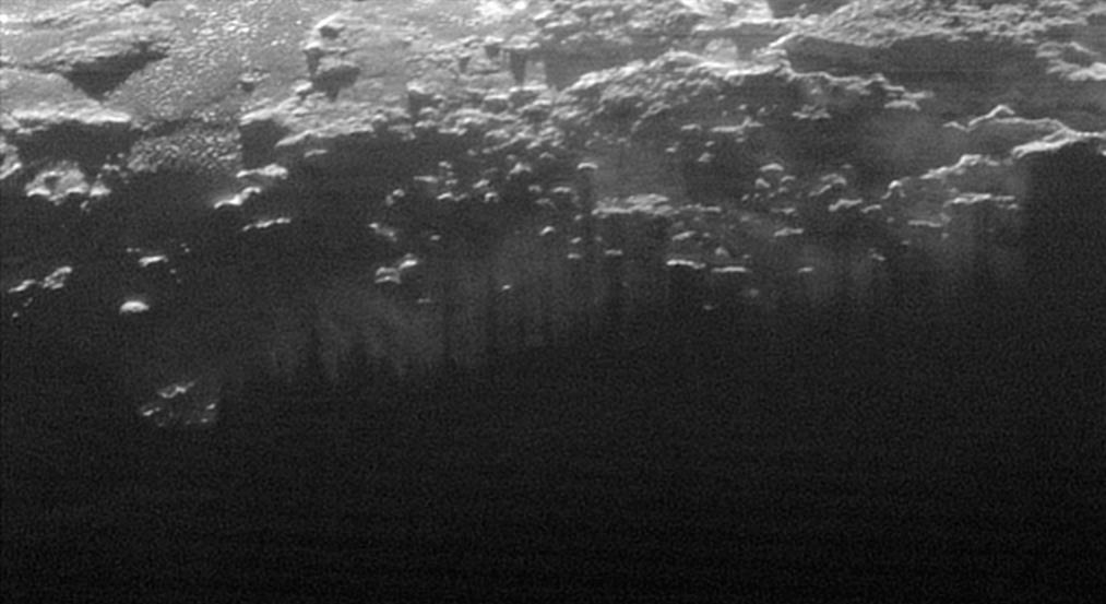 n this small section of the larger crescent image of Pluto, taken by NASA's New Horizons just 15 minutes after the spacecraft's closest approach on July 14, 2015, the setting sun illuminates a fog or near-surface haze, which is cut by the parallel shadows of many local hills and small mountains. The image was taken from a distance of 11,000 miles (18,000 kilometers), and the width of the image is 115 miles (185 kilometers). Credit: NASA/Johns Hopkins University Applied Physics Laboratory/Southwest Research Institute
