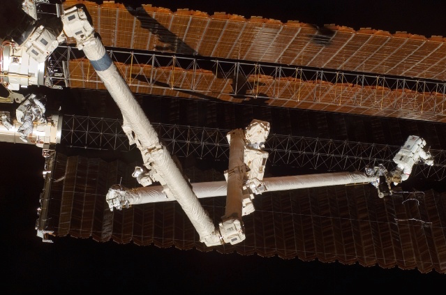 Astronaut Scott Parazynski is seen perched on the end of the space station's robot arm during the shuttle Discovery's visit in November 2007. Parazynski repaired a tear in a solar array with suture-like braces after the wing was damaged during deployment earlier in the mission. Credit: NASA