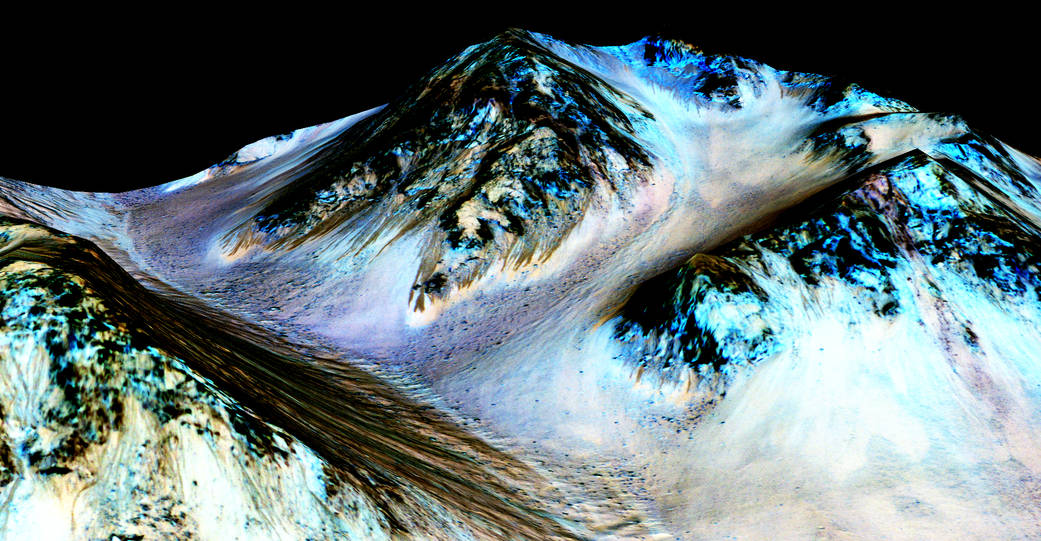 Dark, narrow streaks on Martian slopes such as these at Hale Crater are inferred to be formed by seasonal flow of water on contemporary Mars. The streaks are roughly the length of a football field. The imaging and topographical information in this processed, false-color view come from the High Resolution Imaging Science Experiment (HiRISE) camera on NASA's Mars Reconnaissance Orbiter. Credit: NASA/JPL-Caltech/Univ. of Arizona