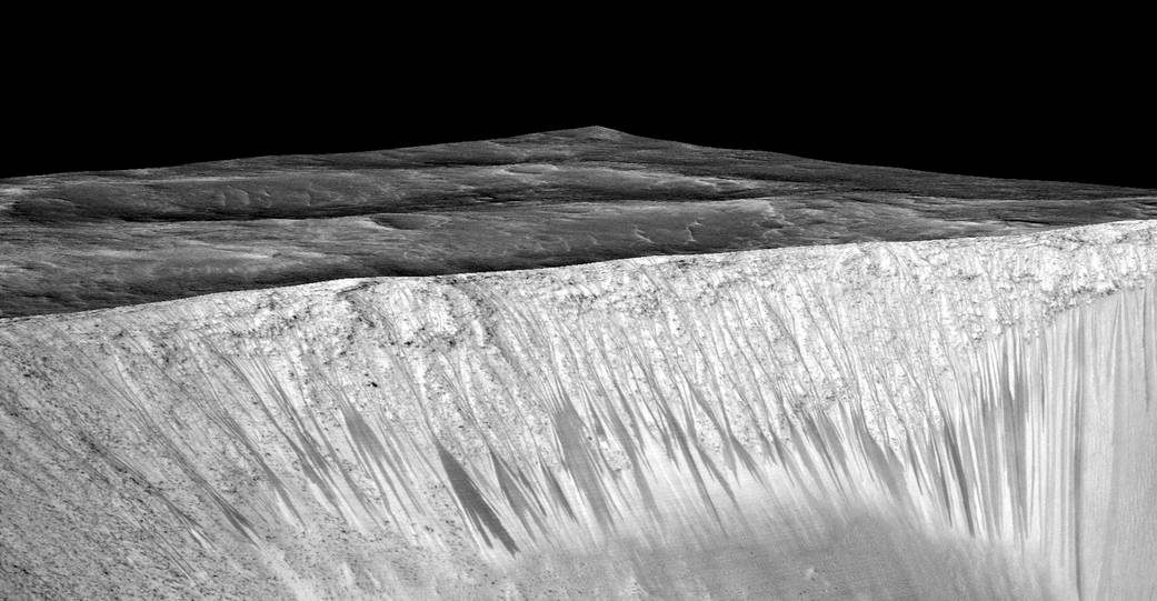 """Dark narrow streaks, called """"recurring slope lineae,"""" emanate from the walls of Garni Crater on Mars, in this view constructed from observations by the High Resolution Imaging Science Experiment (HiRISE) camera on NASA's Mars Reconnaissance Orbiter. The dark streaks here are up to few hundred yards, or meters, long. They are hypothesized to be formed by flow of briny liquid water on Mars. Credit: NASA/JPL-Caltech/Univ. of Arizona"""