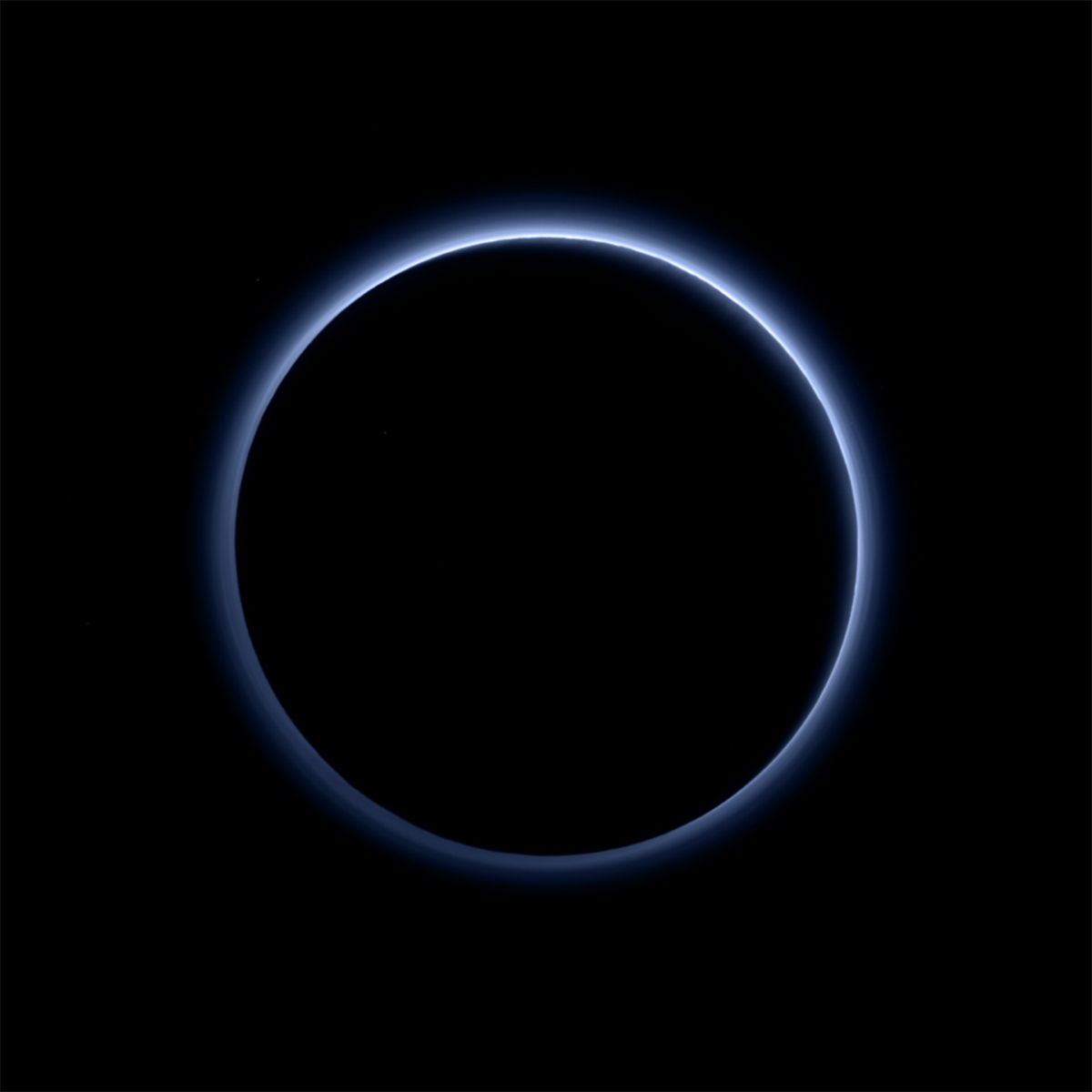 Pluto's haze layer shows its blue color in this picture taken by the New Horizons Ralph/Multispectral Visible Imaging Camera (MVIC). The high-altitude haze is thought to be similar in nature to that seen at Saturn's moon Titan. The source of both hazes likely involves sunlight-initiated chemical reactions of nitrogen and methane, leading to relatively small, soot-like particles (called tholins) that grow as they settle toward the surface. This image was generated by software that combines information from blue, red and near-infrared images to replicate the color a human eye would perceive as closely as possible. Credit: NASA/JHUAPL/SWRI