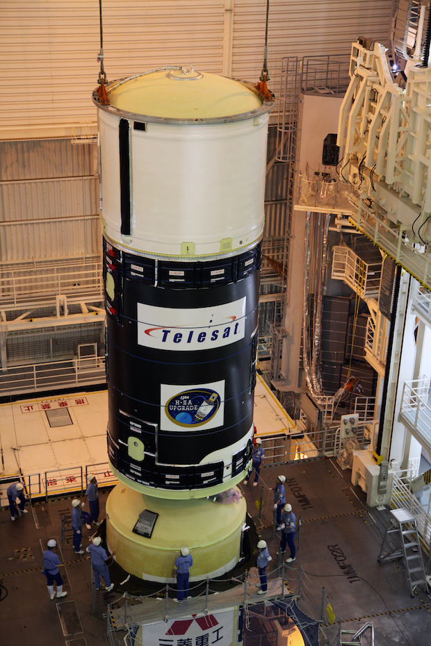 The H-2A's upper stage, seen here with its liquid hydrogen tank painted white, is lifted atop the rocket's first stage inside Tanegashima's vehicle assembly building. Credit: JAXA