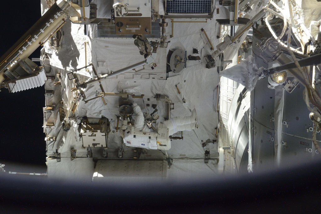 Astronaut Scott Kelly, in an all-white spacesuit, is camouflaged against the space station's structure in this picture taken during Friday's spacewalk by Russian cosmonaut Sergey Volkov. Credit: Sergey Volkov/Roscosmos