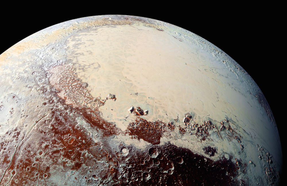 "This high-resolution image captured by NASA's New Horizons spacecraft shows Pluto in exaggerated color to better identify different geologic regions. The bright expanse is the western lobe of the ""heart,"" informally called Sputnik Planum, which has been found to be rich in nitrogen, carbon monoxide and methane ices. Credit: NASA/JHUAPL/SWRI"