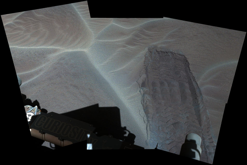 A wheel track left by NASA's Curiosity Mars rover exposes underlying material in a shallow sand sheet in this Dec. 2 view from Curiosity's Mast Camera (Mastcam). The site is close to a large sand dune of similarly dark sand grains. Credit: NASA/JPL-Caltech/MSSS