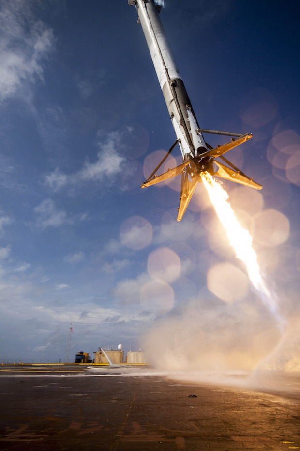 "The Falcon 9's first stage booster descends to a vertical landing on SpaceX's drone ship, christened ""Just Read The Directions,"" in the Pacific Ocean."