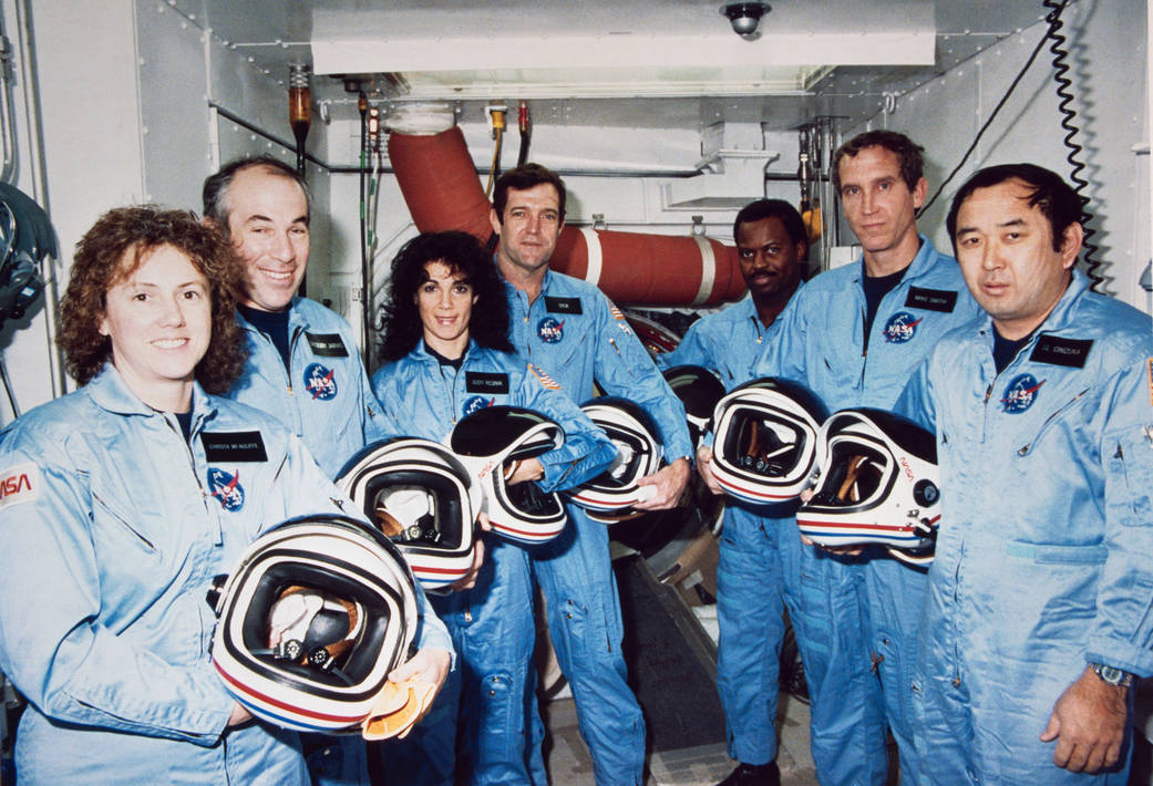 The final crew of the shuttle Challenger takes a break during countdown training in January 1986 to pose for a photo at the launch pad. Credit: NASA