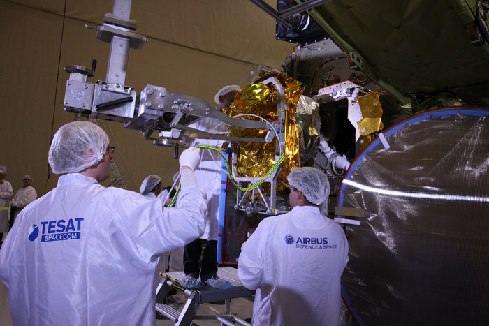 Technicians attach the EDRS laser communications terminal to the Eutelsat 9B satellite. Credit: Airbus Defense and Space