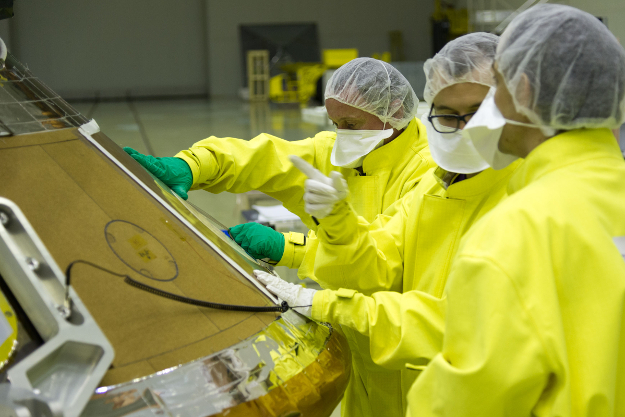 Specialists from Airbus Defense and Space bond tiles to the outer surface of the Schiaparelli lander. Credit: ESA - B. Bethge