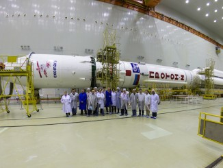 Ground teams pose for a picture with the fully assembled Proton rocket with the ExoMars Trace Gas Orbiter and Schiaparelli lander. Credit: Khrunichev