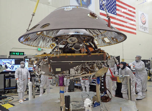 The back shell of the InSight spacecraft is lowered onto the lander in a clean room at Lockheed Martin. Credit: NASA/JPL-Caltech/Lockheed Martin