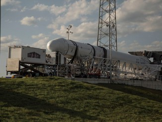 SpaceX's Falcon 9 rocket sits horizontal as technicians install late-load cargo into the Dragon capsule. Credit: SpaceX