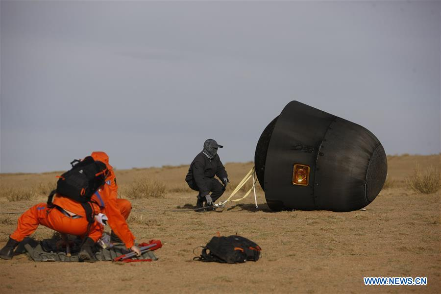 Chinese technicians greet the Shijian 10 landing module after its touchdown Monday in the Inner Mongolia region. Credit: Xinhua