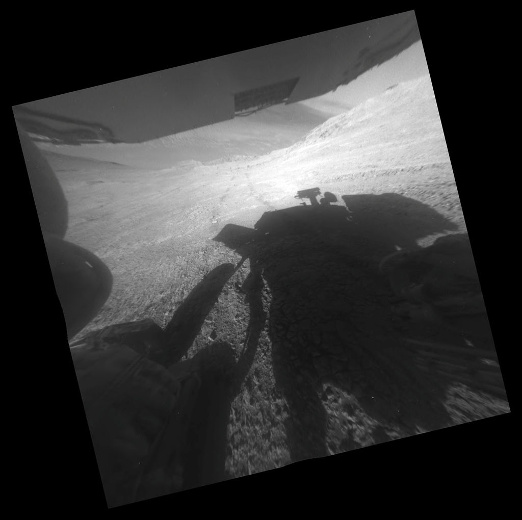 "A shadow and tracks of NASA's Mars rover Opportunity appear in this March 22, 2016, image, which has been rotated 13.5 degrees to adjust for the tilt of the rover. The hillside descends to the left into ""Marathon Valley."" The floor of Endeavour Crater is seen beneath the underside of a solar panel. Credit: NASA/JPL-Caltech"