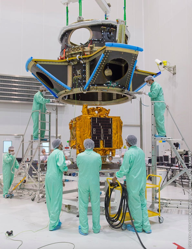 Technicians lower the Soyuz rocket's auxiliary payload support structure over the Microscope satellite at the Guiana Space Center. Credit: ESA/CNES/Arianespace – Photo Optique Video du CSG – S. Martin