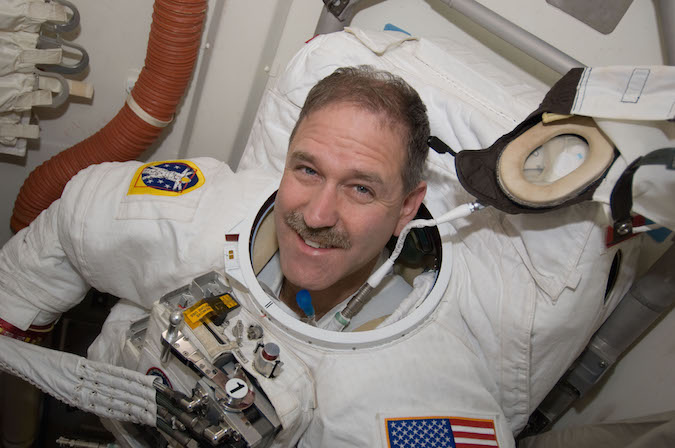 John Grunsfeld is seen inside the shuttle Atlantis' airlock preparing for a spacewalk during a 2009 visit to the Hubble Space Telescope. Credit: NASA