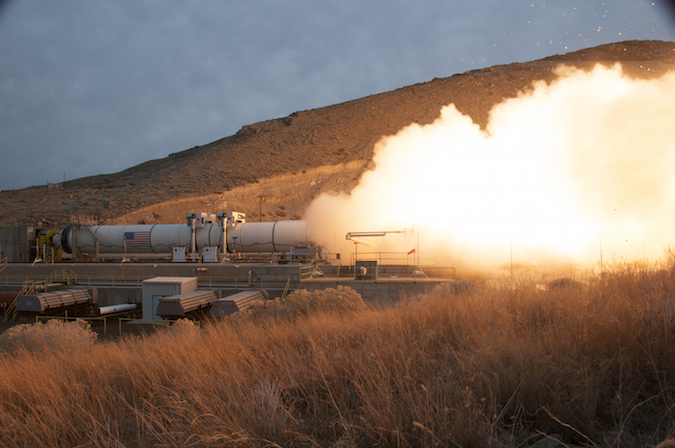 A fivei-segment solid rocket motor designed as a strap-on booster for NASA's Space Launch System undergoes a test firing at Orbital ATK's Utah plant. The company's Next-Generation Launcher would use a derivative of the booster with composite casings and only two or four segments. Credit: NASA