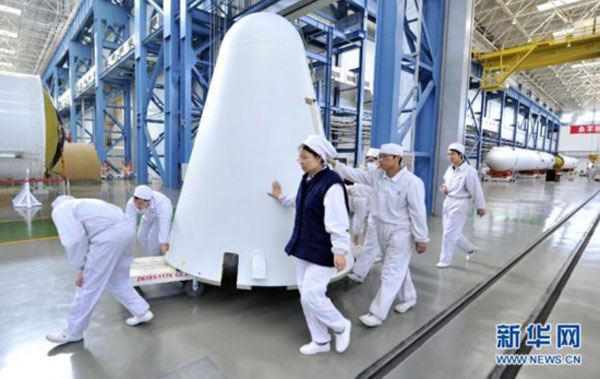 Chinese aerospace technicians are pictured with a nose cone for one of the Long March 7 rocket's strap-on boosters. Credit: Xinhua