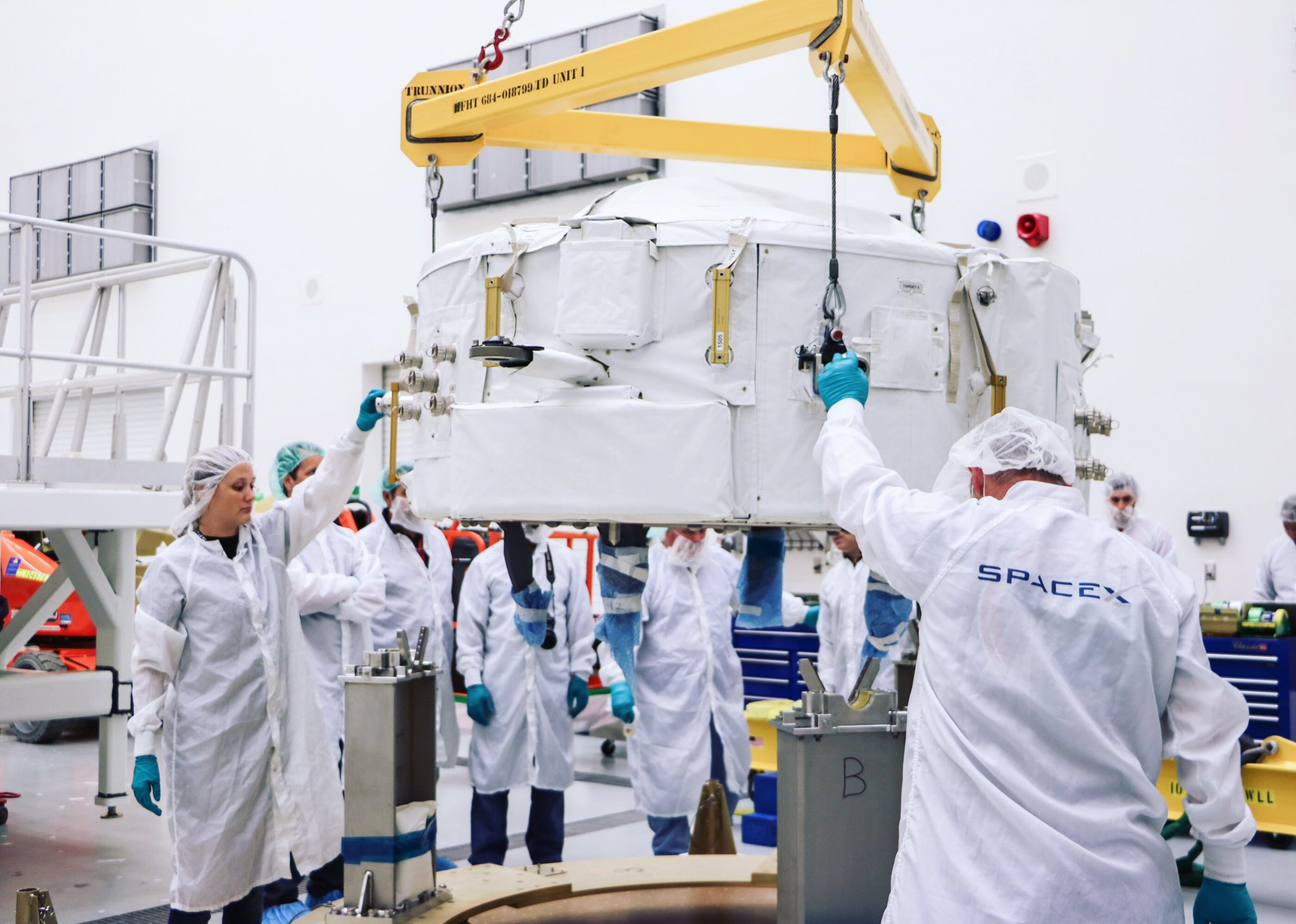 Technicians prepare a Boeing-built International Docking Adapter before its launch Monday. Credit: SpaceX