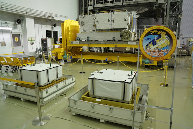 Two of the six lithium-ion batteries set for launch on Japan's sixth HTV cargo mission are seen in a clean room at the Tanegashima Space Center. The HTV's exposed pallet in the background already holds four of the batteries. Credit: JAXA