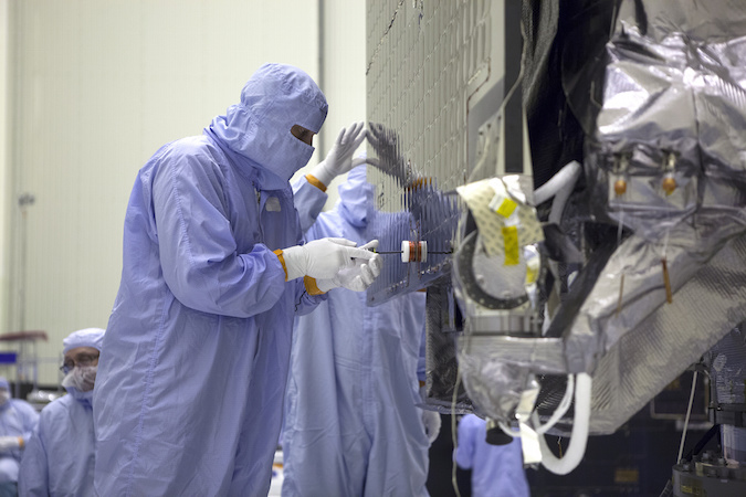 Technicians and engineers install a solar panel on the OSIRIS-REx spacecraft. Credit: NASA/Ben Smegelsky