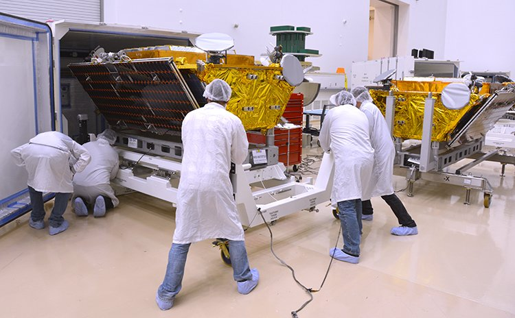 Technicians load the first two Iridium Next satellites into their shipping containers at Orbital ATK's manufacturing facility in Gilbert, Arizona. Credit: Iridium