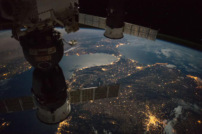 A Soyuz crew ferry craft (left) and a Progress supply ship (right) are docked with the International Space Station in this view captured during a night pass over Europe. The Strait of Gibraltar is visible in the background. Credit: NASA