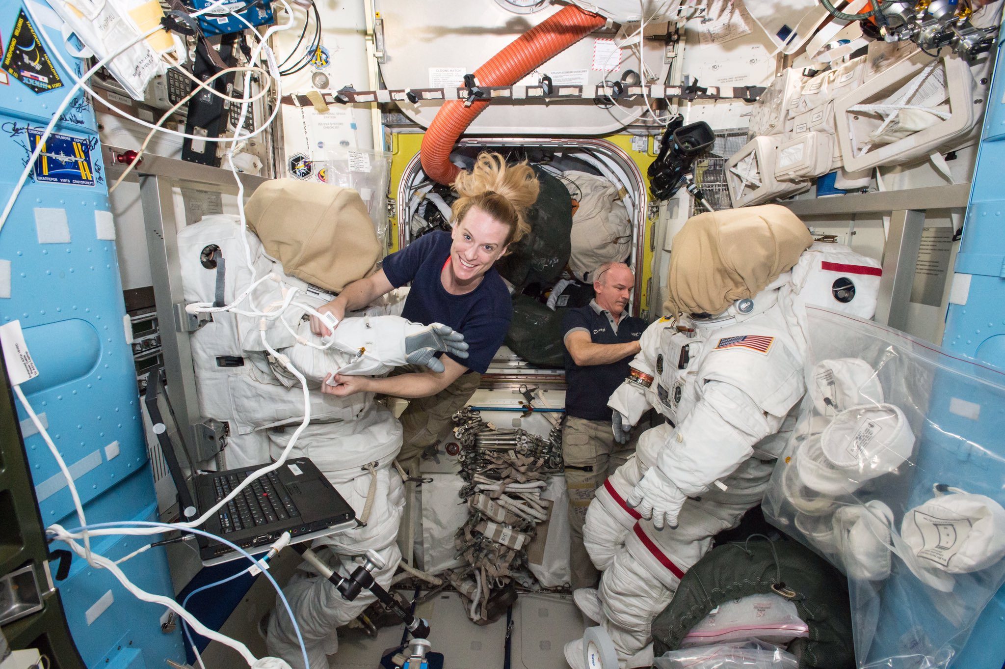 Kate Rubins (left) and Jeff Williams (right) work with spacesuits aboard the International Space Station. Credit: NASA