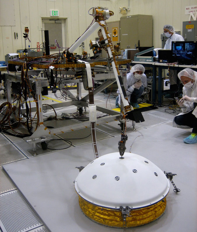 InSight's robotic arm will place the seismometer instrument on the surface of Mars to detect quakes. In this image, the arm works with an engineering model of the seismometer instrument package. Credit: NASA/JPL-Caltech