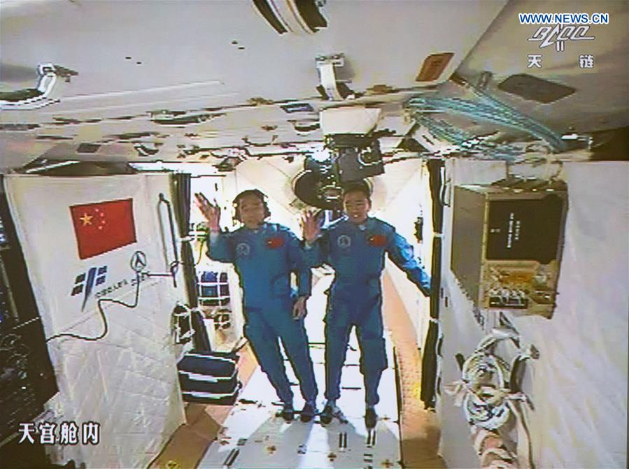Jing Haipeng (left) and Chen Dong (right) wave to ground controllers after entering Tiangong 2. Credit: Xinhua