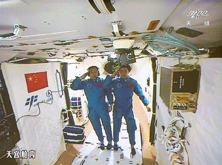 Astronauts Jing Haipeng (left) and Chen Dong (right) salute ground controllers in this view inside the Tiangong 2 space lab. Credit: Xinhua
