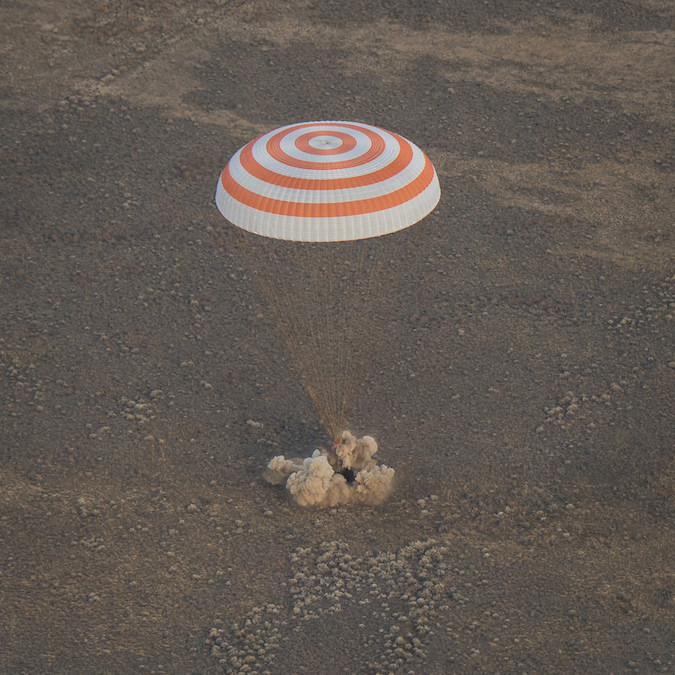 """The Soyuz MS-01 spacecraft touches down cushioned by """"soft landing"""" rockets at 0358 GMT (11:58 p.m. EDT). Credit: NASA/Bill Ingalls"""