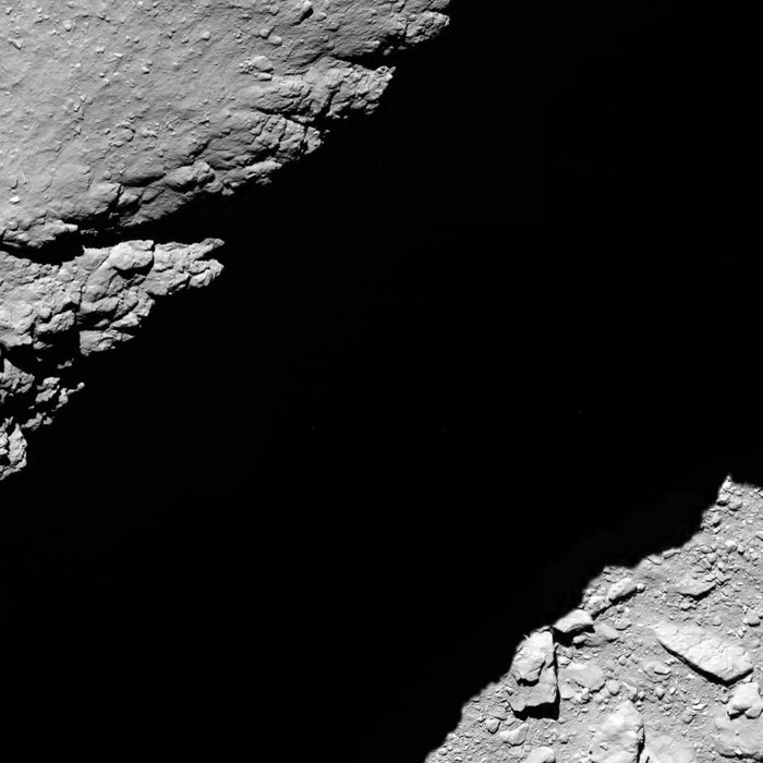 Rosetta's OSIRIS narrow-angle camera recorded this image of comet 67P/Churyumov-Gerasimenko from a distance of less than 4,000 feet (1.2 kilometers) at 1014 GMT (6:14 a.m. EDT) on Sept. 30. The image shows part of the wall of the Deir el-Medina pit in shadow. The field-of-view stretches about 110 feet (33 meters) across, and the resolution is about 0.9 inches (2.3 centimeters) per pixel. Credit: ESA/Rosetta/MPS for OSIRIS Team MPS/UPD/LAM/IAA/SSO/INTA/UPM/DASP/IDA