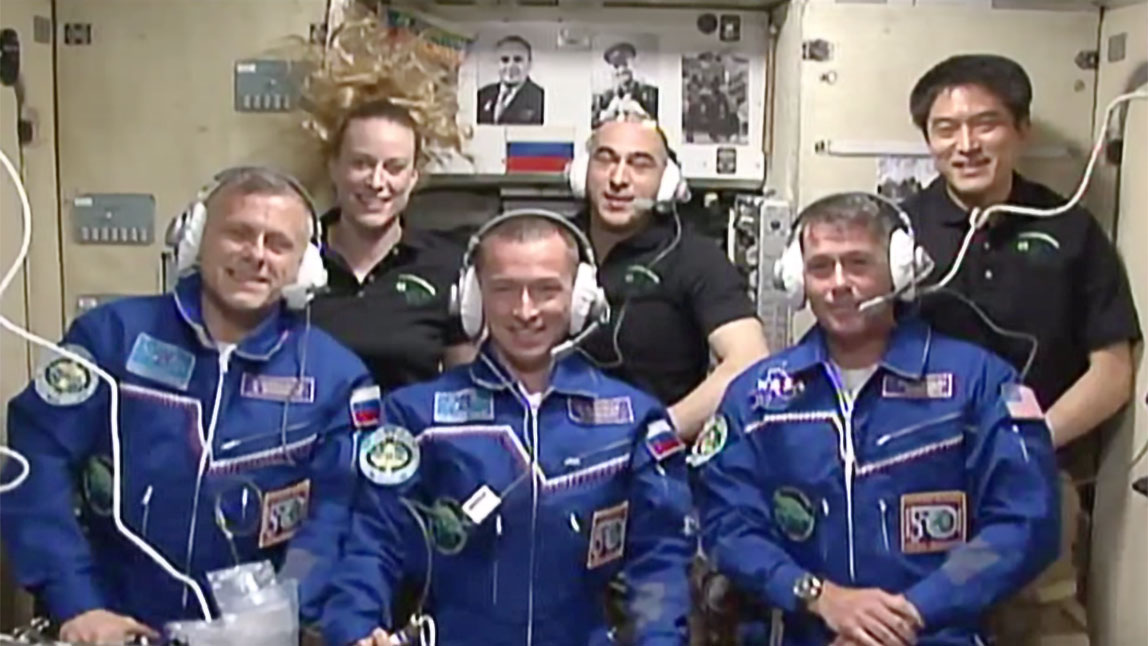 The new six-member Expedition 49 crew gathers in the Zvezda service module. The three newest arrivals (front row from left) Andrey Borisenko, Sergey Ryzhikov and Shane Kimbrough talk to family members and mission officials back on Earth. In the back row from left are, Kate Rubins, Anatoly Ivanishin and Takuya Onishi. Credit: NASA TV