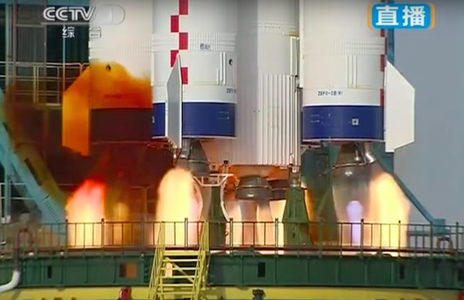 The Long March 2F rocket's first stage and four liquid-fueled boosters ignite and throttle up to 1.4 million pounds of total thrust.